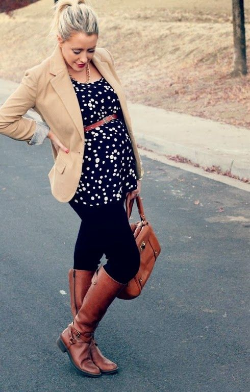 black jeans, a dotted flowy top, brown boots and a tan jacket