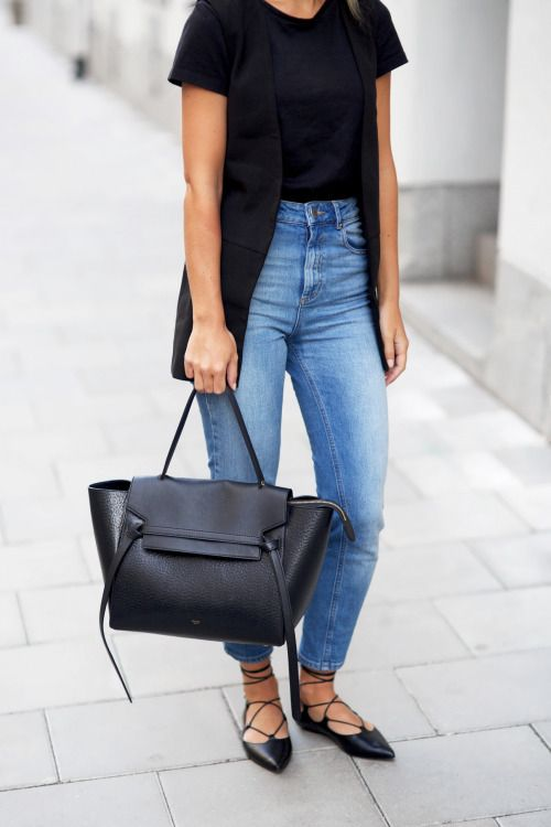 black tee tucked into jeans, a black vest and lace up flats work outfit