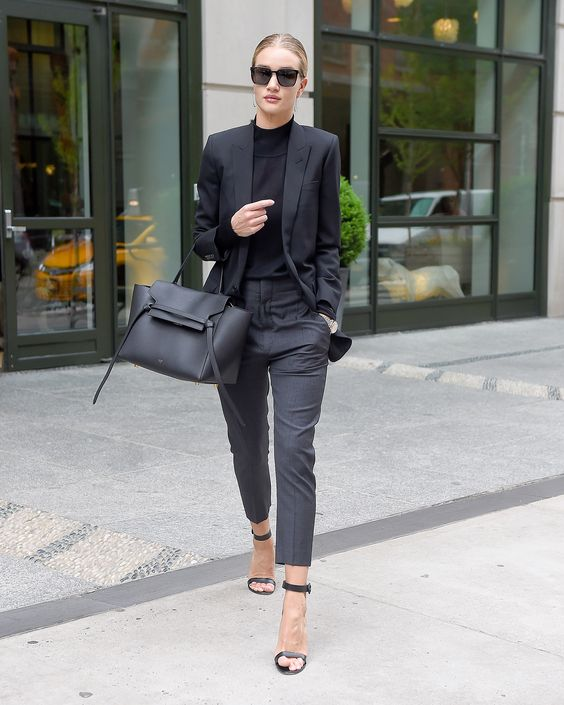 a black blazer and top, grey trousers and black heels