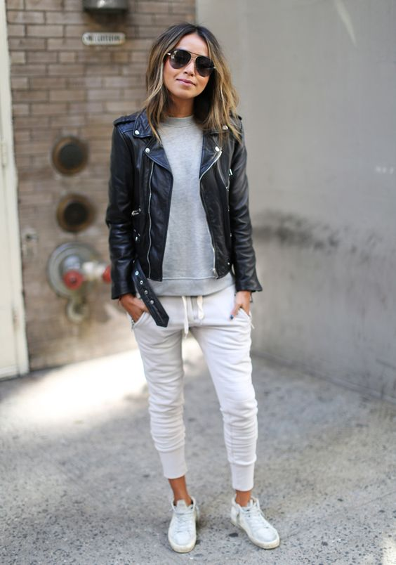 black sport trousers, a grey sweatshirt, white sneakers and a black leather jacket