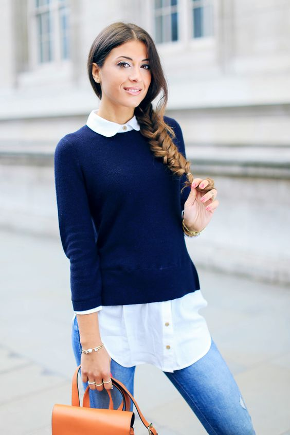 blue distressed jeans, a black sweater and a white shirt