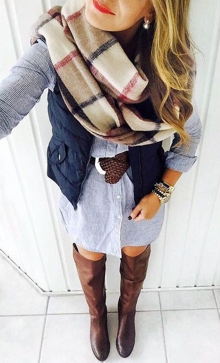 chambray button up dress, brown riding boots, a navy vest, brown belt, and a blanket scarf