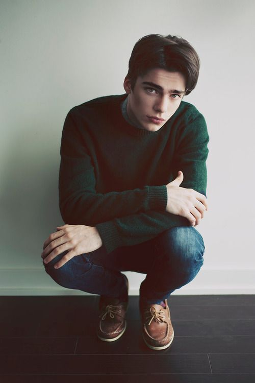 blue jeans, a fitted green sweater and brown shoes