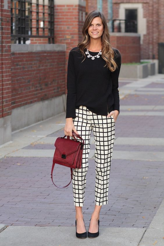 a black shirt, checked trousers, black heels and a burgundy bag