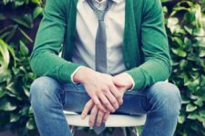 10 blue jeans, a white shirt, a grey tie and a green cardigan with brown shoes