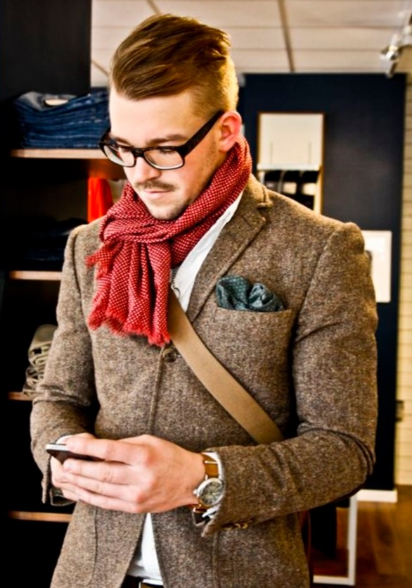 a brown blazer, a red scarf and glasses
