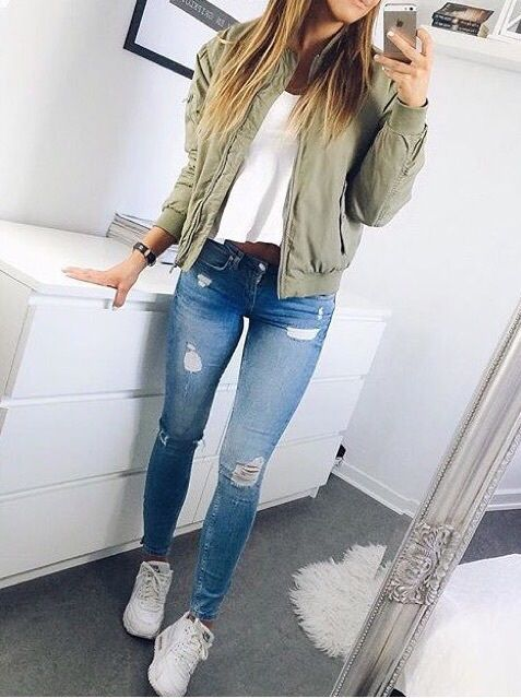blue jeans, a white top, an olive green moto jacket