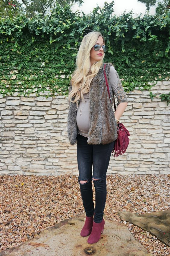 brown shirt, black distressed denim, a faux fur vest, burgundy boots and a bag