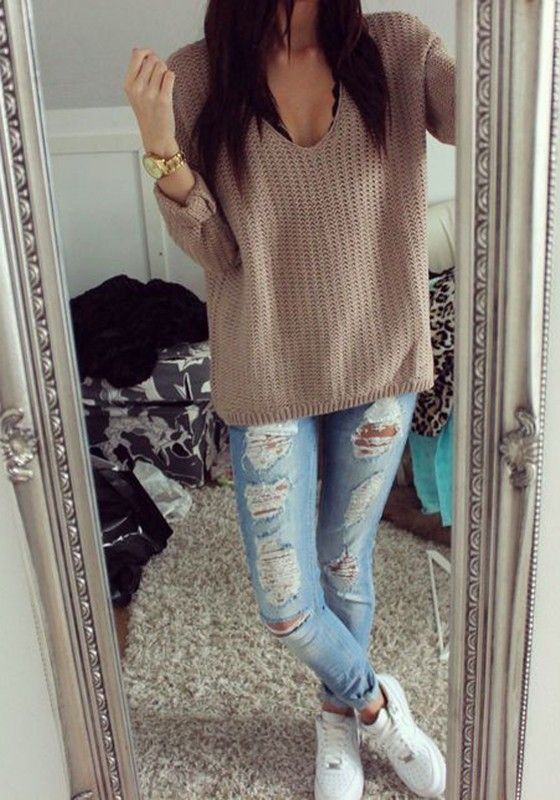 distressed jeans, a V-neck sweater and white Converse