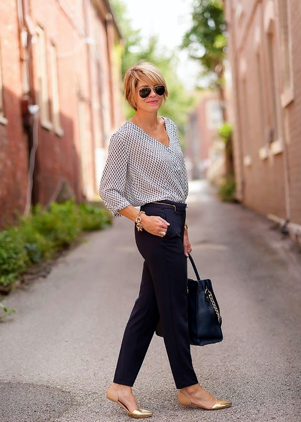 navy trousers, a printed blouse, gold flats
