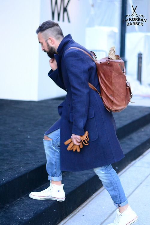 ripped blue jeans, a long blue coat and a brown backpack