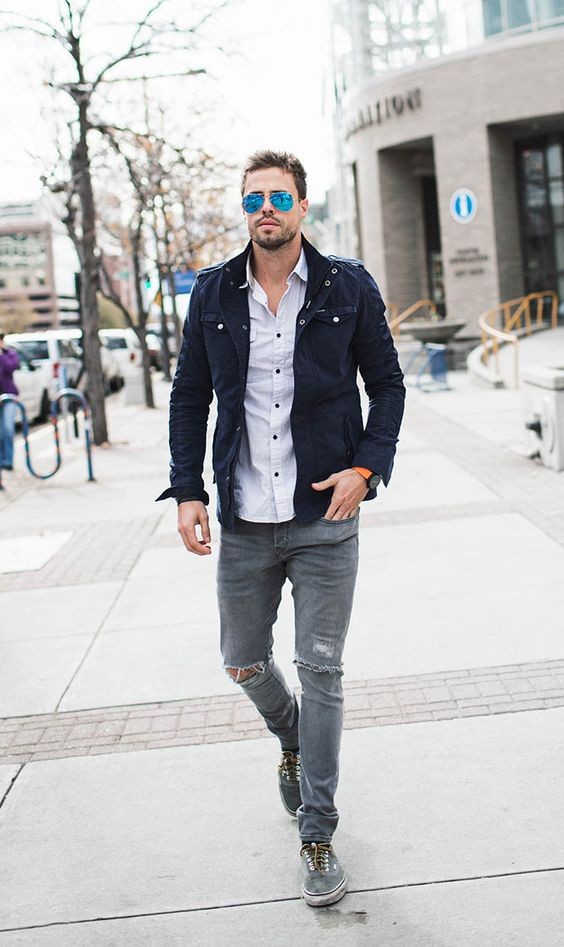 ripped grey jeans, a light shirt, a navy jacket and grey sneakers