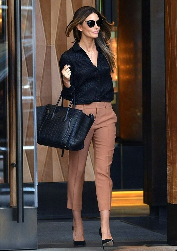 tan trousers, a black blouse and black pumps