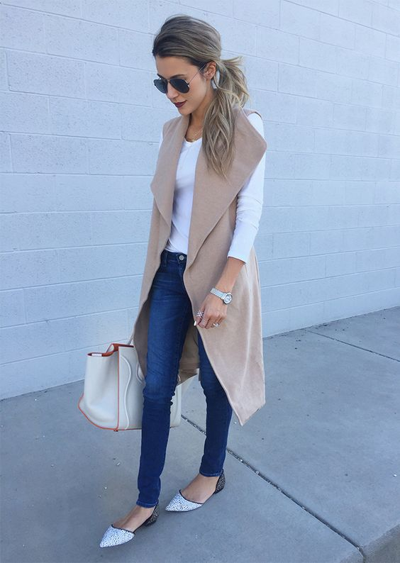 sleeveless camel coat, blue jeans, a white long sleeve and dotted flats