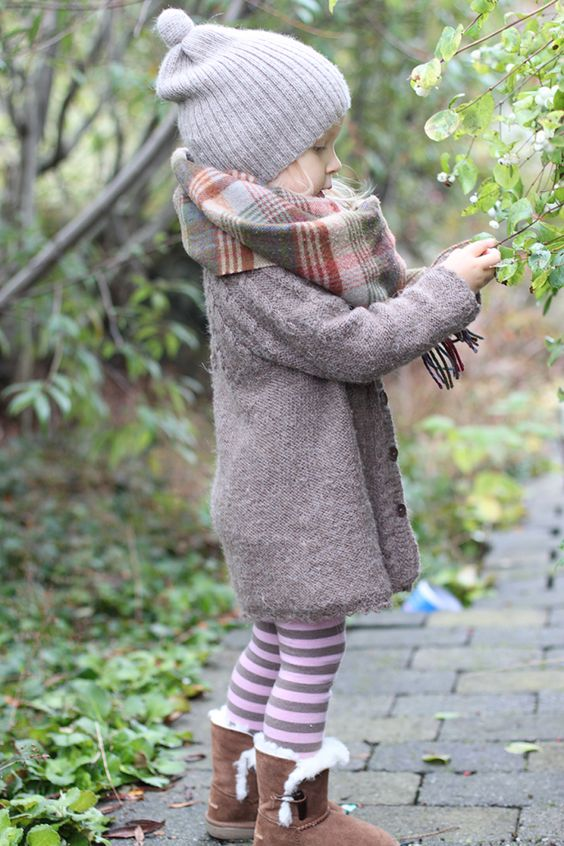 knit coat, striped leggings, fur boots, a plaid scarf and a knit hat