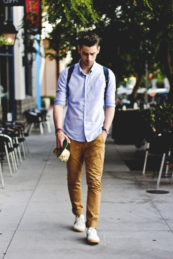 ocher trousers, a blue shirt and white sneakers are a perfect early fall outfit