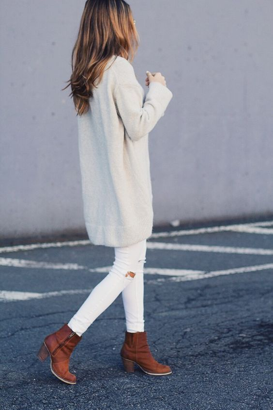 ripped white jeans, a long white cardigan and brown ankle booties