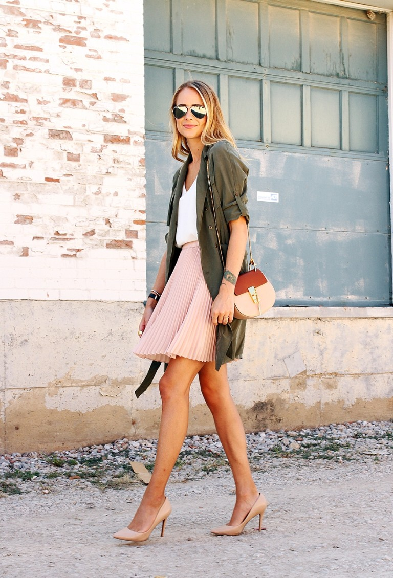 a blush skirt, a white top, a military coat and nude shoes