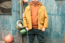 22 green trousers, an orange swetshirt, brown boots, a yellow jacket