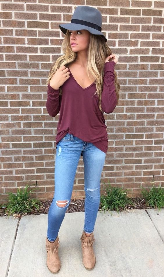 ripped blue jeans, a burgundy shirt and brown fringe boots