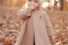 23 nude coat, black leggings and a white knit hat