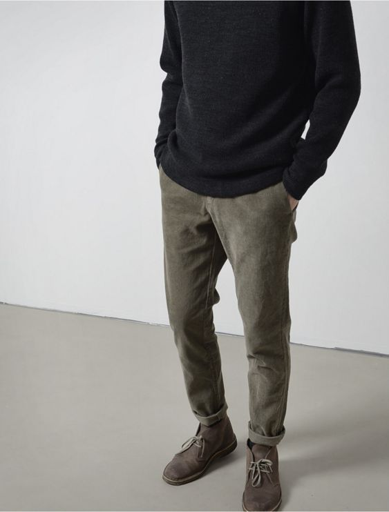 olive grey trousers, a black sweater and brown boots