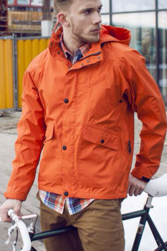 brown pants, a plaid shirt and an orange rain jacket