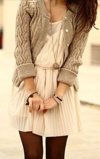 a white pleated dress, a grey cardigan and black tights
