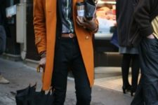 29 ocher coat, black pants, a printed shirt and brown boots