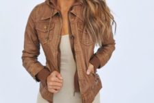 30 zippered brown leather jacket, ripped black jeans and a nude top