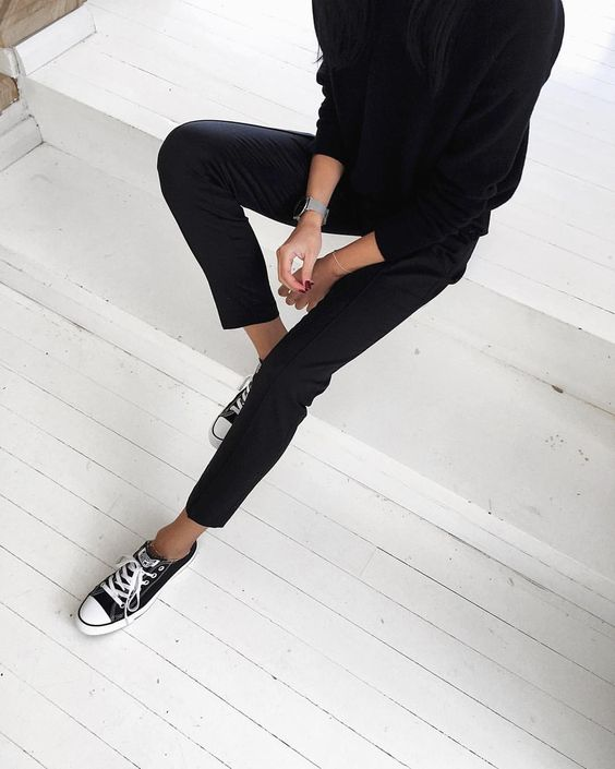 minimal all-black look with black trousers and a black sweater