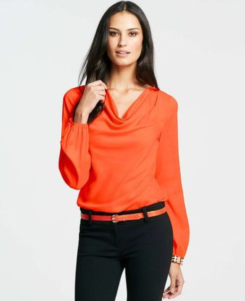 Orange blouse with orange belt and black trousers