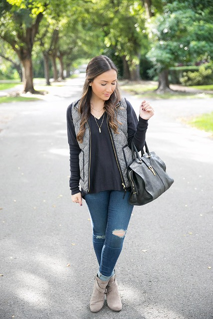 With black loose blouse, distressed jeans and gray boots