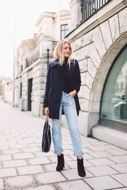 With black shirt, cuffed jeans and black ankle boots