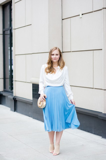 With blue pleated skirt, neutral sandals and mini bag