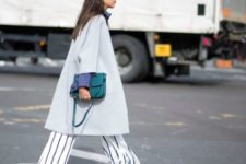 With light gray coat, boots and colored bag