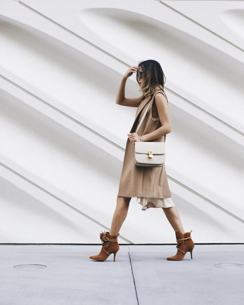With white dress, beige long vest and white bag