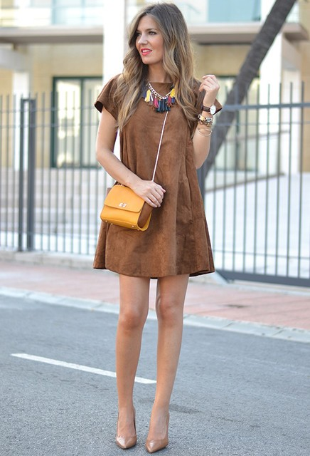 With yellow bag, neutral pumps and statement necklace