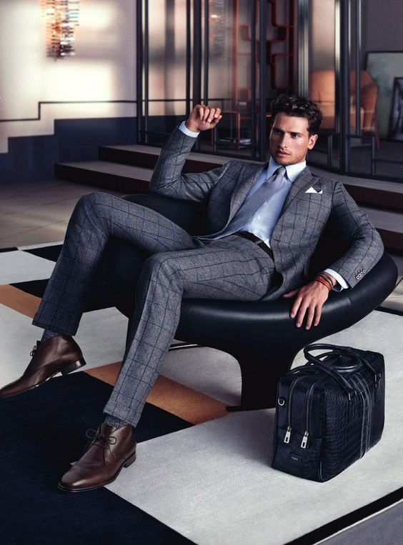 checked grey suit, a blue shirt and brown boots