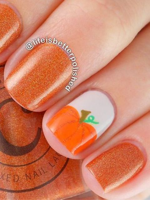 glitter orange nails with a pumpkin accent
