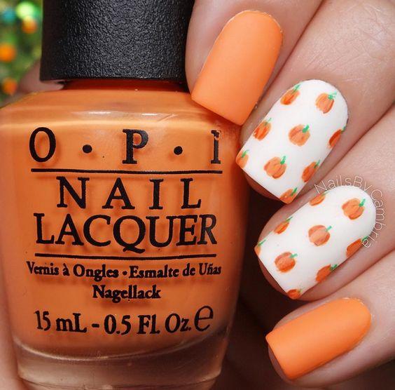 orange matte nails with pumpkin accents