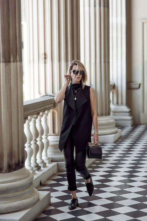 leather pants, a turtleneck, a long vest and flat shoes