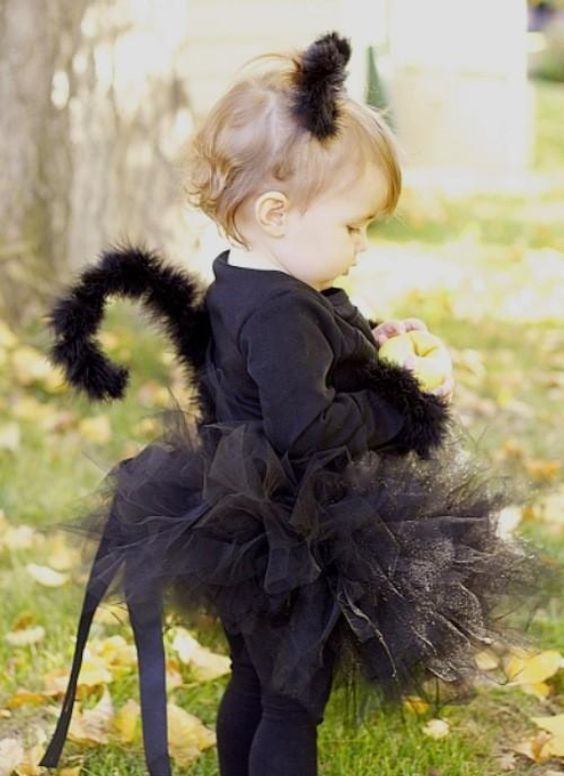 black cat with a tulle skirt, ears and a tail