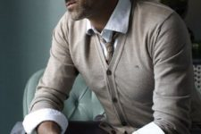 14 grey pants, a beige cardigan, a shirt with cuffed sleeves and a tie
