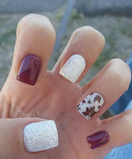 fall nails with white glitter, burgundy and a leaf accent nail