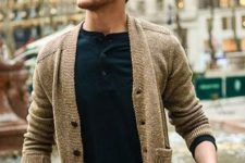 17 warm tan cardigan, a black tee with buttons and jeans