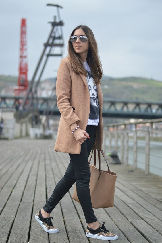 leather pants, a printed tee, a camel coat and leopard Vans