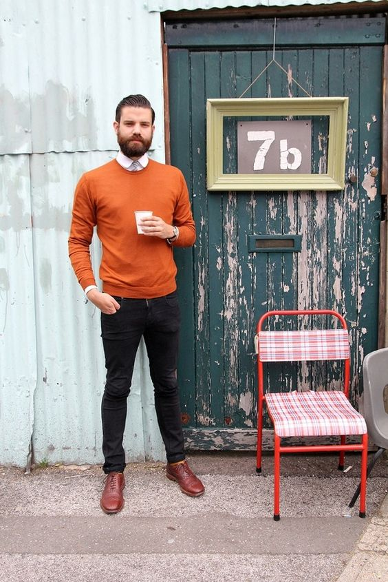 orange sweater, a white shirt with a tie and brown shoes