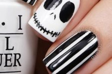 21 striped black and white manicure with a jack-o-lantern accent nail