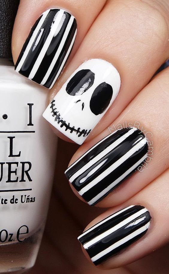 striped black and white manicure with a jack-o-lantern accent nail